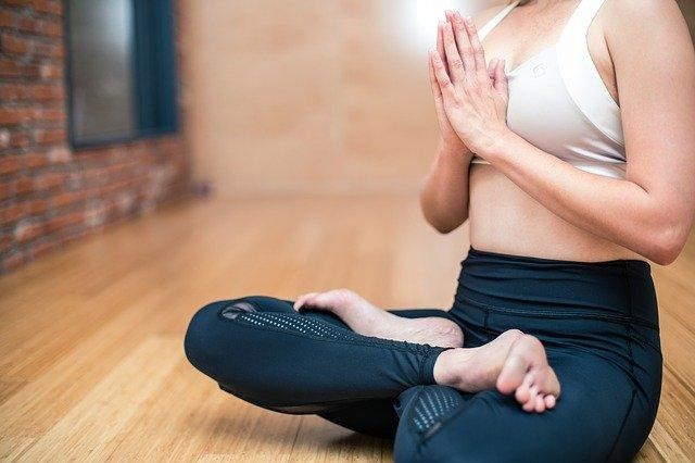 A woman practicing yoga, one of the best approaches for staying healthy while traveling.