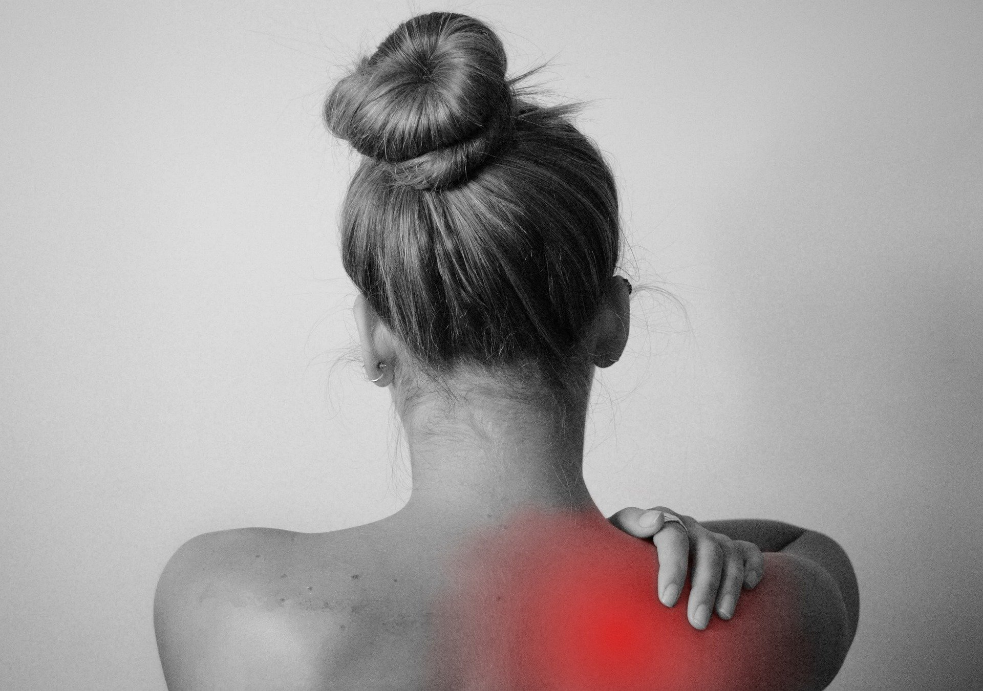A black and white view of a woman with back pain.